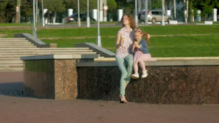 шишка : Mom and daughter eating ice cream in a park. mother and child. relaxing happy family