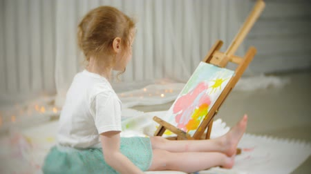 холст : Beautiful red-haired girl sits on the floor in the studio in front of the easel and draws a brush and colored paints Стоковые видеозаписи