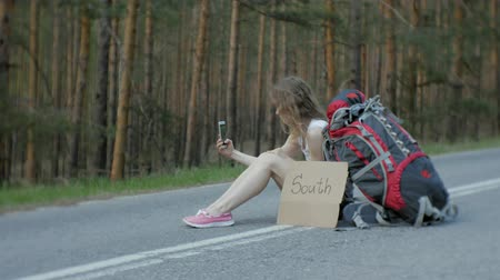 országúti : Young beautiful woman hitchhiking standing on the road with a backpack on a table with an inscription SOUTH Stock mozgókép