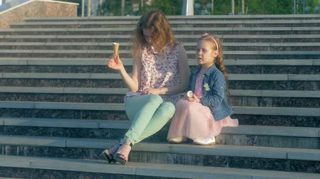 kužel : Mom and daughter eating ice cream in a park. mother and child. relaxing happy family