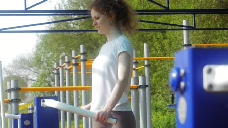 horizontal bar : young fitness woman doing exercises on the gym in an outdoor park