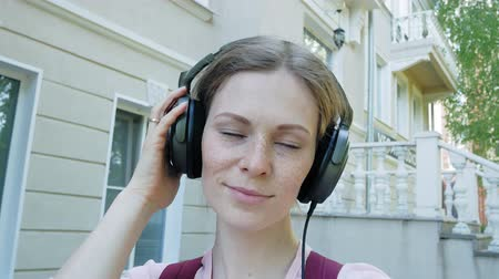 sorriso largo : young stylish beautiful woman, on city streets listening to music in large monitor headphones.