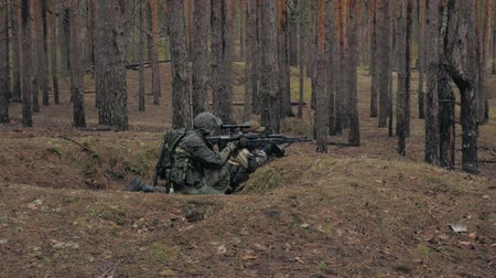zbraň : Soldiers in camouflage with combat weapons are being fired in the shelter of the forest, the military concept