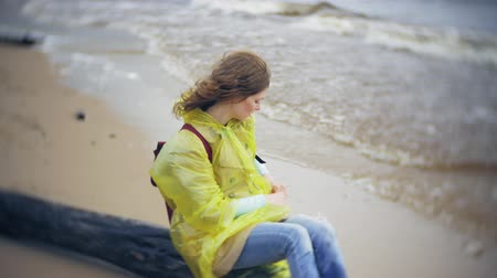 raincoat : Happy woman walking along the coast Traveling Lifestyle adventure vacation outdoors. A girl dressed in a fashionable yellow raincoat