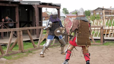 rytíř : Knights in steel armor and chain mail helmets fighting at medieval tournament