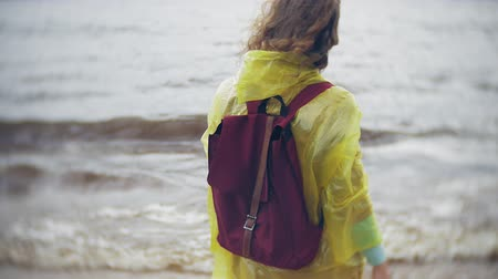 wanderlust : Happy woman walking along the coast Traveling Lifestyle adventure vacation outdoors. A girl dressed in a fashionable yellow raincoat