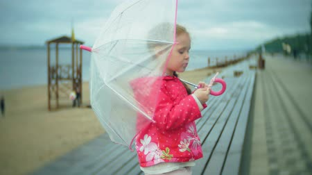 raincoat : Little beautiful girl with umbrella playing in the rain eating ice cream on the coast