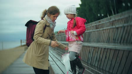 raincoat : Little beautiful girl and her mother with umbrella playing in the rain