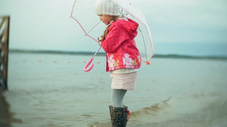 raincoat : Little beautiful girl with umbrella, playing in the rain, walking along the coast