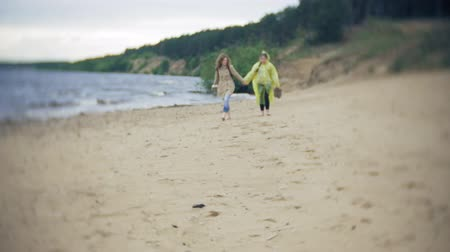 raincoat : Happy girl walking along the coast Traveling Lifestyle adventure vacation outdoors. A girl dressed in a fashionable yellow raincoat