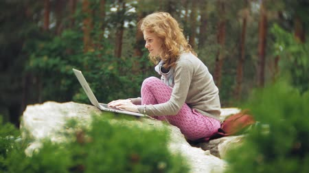benches : A woman with a laptop relaxes on the rocks in a beautiful green park. A young perennial woman in an arboretum working behind a laptop. Technology in the open air