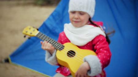 ukulele : A beautiful girl with her family plays on a ukulele on the river bank near a tourist tent Stock Footage