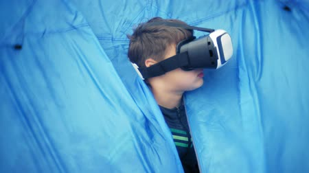 grau : A small boy uses a helmet for a virtual reality headset, a beach near a tourist tent Stock Footage