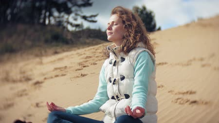 religion health : Woman sitting in a lotus yoga pose on the sand near the water Stock Footage