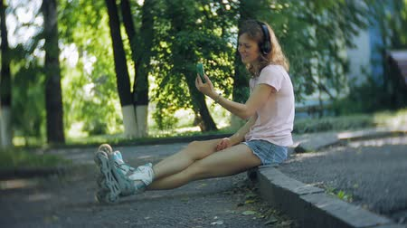 plavé vlasy : woman rollerblading and listening to music on headphones on the phone in the park