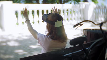 kártyás : Young woman uses head-mounted display in the park. Playing game using VR-helmet for smart phones. Happy Stock mozgókép