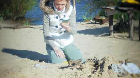 make photo : The woman is engaged in excavating bones in the sand, Skeleton and archaeological tools. Makes photo on smartphone Stock Footage