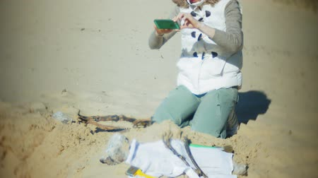 dinosaurus : The woman is engaged in excavating bones in the sand, Skeleton and archaeological tools. Makes photo on smartphone Dostupné videozáznamy