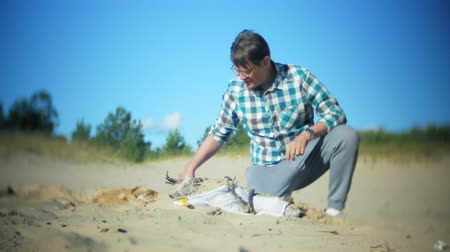 dino : The man is engaged in excavating bones in the sand, Skeleton and archaeological tools.
