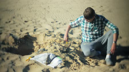 dinosaur : The man is engaged in excavating bones in the sand, Skeleton and archaeological tools.