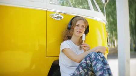 attitude : young woman outdoors by yellow vagon car listening music in headphones using smartphone - relaxing, enjoying, concept of technology and travel