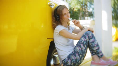 authenticity : young woman outdoors by yellow vagon car listening music in headphones using smartphone - relaxing, enjoying, concept of technology and travel