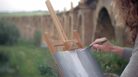 arno : Young woman draws on the easel paints and brush old vintage bridge