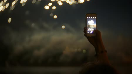 эпический : spectators with smartphones. Photograph firework on the phone, close-up hands