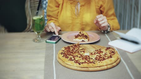 limão : A young woman eats a pie in a cafe bar and uses a telephone Vídeos