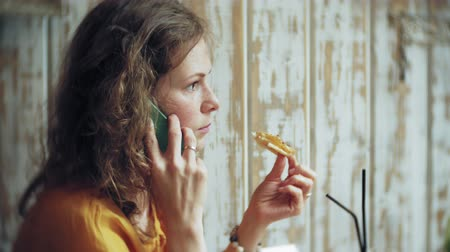 a healthy lifestyle : A young woman eats a pie in a cafe bar and uses a telephone Stock Footage