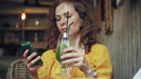uses : A young woman drinks a cocktail at a cafe bar and uses a telephone Stock Footage
