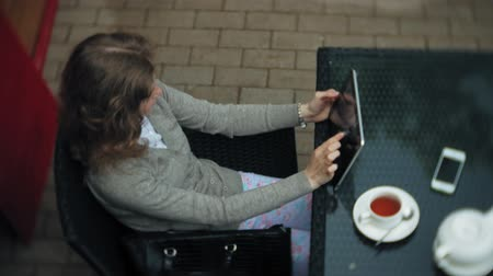 takes : Young woman uses a tablet and phone, drinks tea in a cafe bar Stock Footage