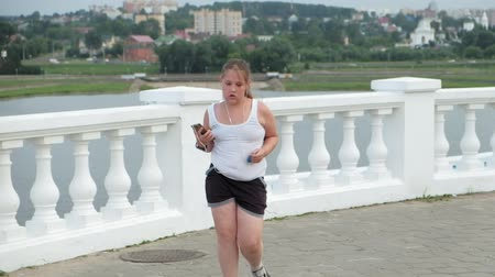 проливая : Young fat girl running, shedding weight, listening to music in headphones concept of healthy lifestyle