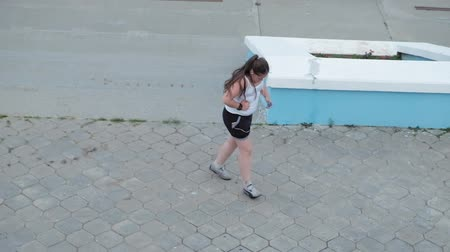 проливая : Young fat girl running down stairs, shedding weight, listening to music in headphones concept of healthy lifestyle super slow motion
