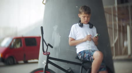 reaching : The boy sits on a BMX bike and listens to music from a smartphone Stock Footage