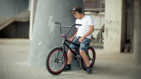 достигать : The boy sits on a BMX bike and listens to music from a smartphone Стоковые видеозаписи