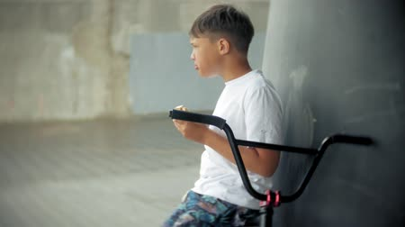 достигать : The boy sits on a BMX bike and eats with a hotdog appetite