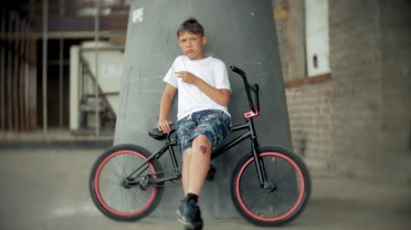 reaching : The boy sits on a BMX bike and eats with a hotdog appetite