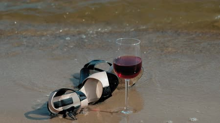footwear : shoes lie on the seashore, a glass of wine lies beside