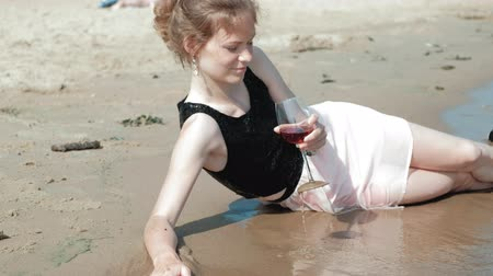 alkoholismus : drunk woman lies on the beach with a glass of wine after a party