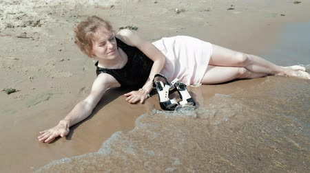 bêbado : drunk woman lies on the beach with a glass of wine after a party