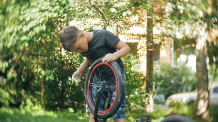 oneperson : The boy washes his  bicycle with water and foam