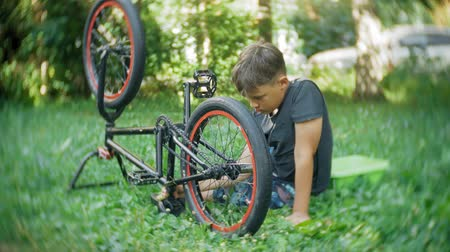 oneperson : The boy washes his BMX bicycle with water and foam
