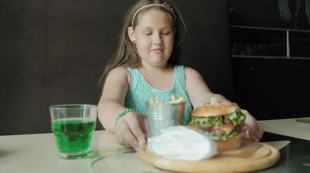 круглолицый : fat girl eagerly eating a hamburger, concept of a healthy diet