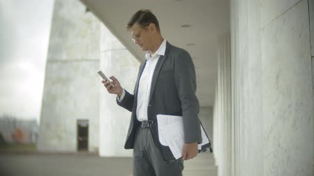 comunicações globais : Businessman in the city. He wears a suit and briefcase. He looks through documents and talks on the smartphone