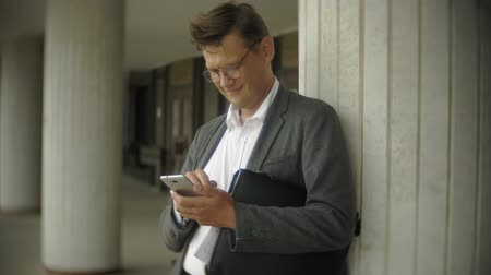 negócios globais : Businessman is sitting on the stairs in the city. He wears a suit and briefcase. He looks through documents and talks on the smartphone Vídeos