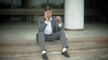 dull : Businessman is sitting on the stairs in the city. He wears a suit and briefcase and talks on the smartphone