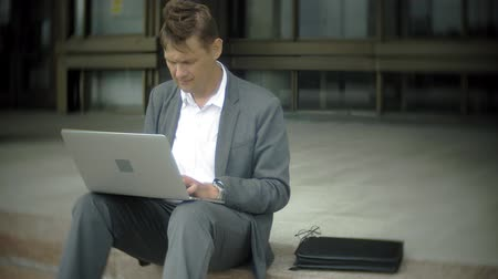 formální : Businessman is sitting on the stairs in the city. He wears a suit and briefcase. He works on a laptop