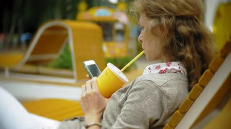молочный коктейль : Young woman with milkshake and cell phone outdoors on a comfortable creative bench