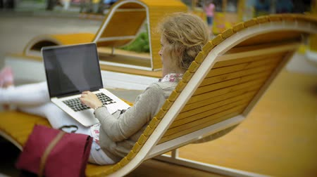 bank : Young woman with milkshake and laptop outdoors on a comfortable creative bench Stok Video